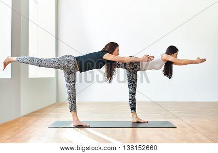 Two young women doing yoga asana Warrior III Pose. Virabhadrasana III