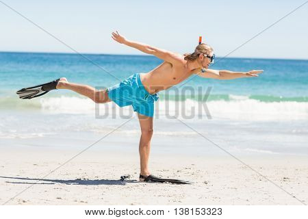 Man posing with diving mask and flippers on beach