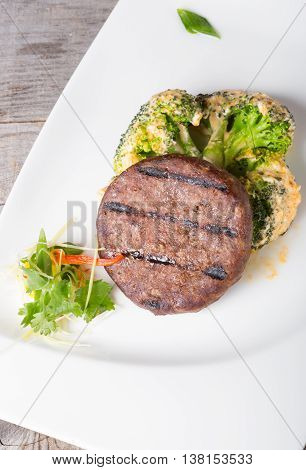 Fried beef cutlet served with broccoli garnish