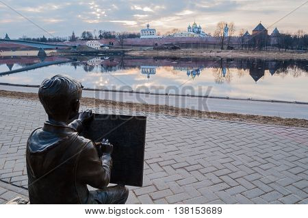 VELIKY NOVGOROD RUSSIA -MARCH 26 2016. Architecture landscape - sculpture of the painter boy drawing the Novgorod Kremlin in front of the Volkhov river. Selective focus at the sculpture