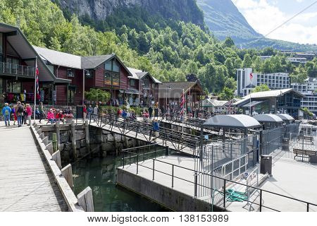 GEIRANGER, NORWAY - JUNE 29: Tourists  walking through the seaport quay on June 29, 2016 in Geiranger, Norway. Geiranger is UNESCO heritage site.
