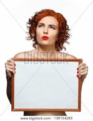 Young red-haired woman anxiously looking up and holding a white plate in the hands of