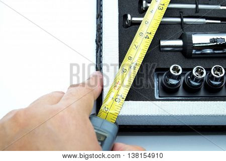Close up of corner of tool box with screwdriver, adjustable torque, steel tape measure with hand. Isolated on white. Space for texts.