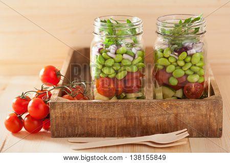 healthy vegetable salad in mason jar: tomato, cucumber, soybean, onion