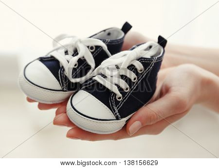 Female hands holding baby shoes, close up