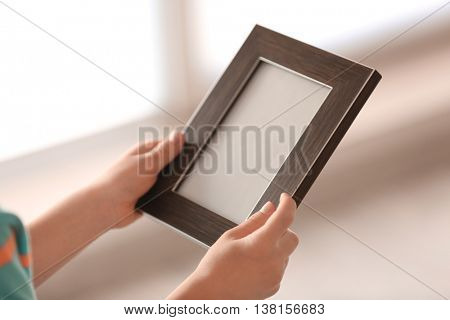 Child's hands holding photo frame on light background