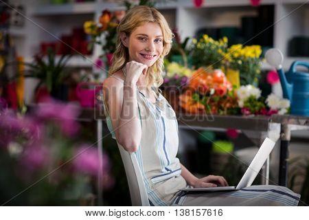 Portrait of smiling female florist using laptop in florist shop