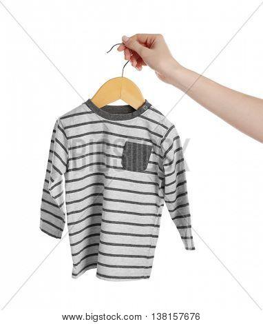 Female hand holding baby shirt on white background
