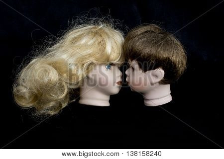 Girl and Boy Doll Head Kissing on black background