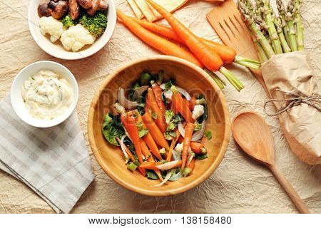 Salad with baby carrot in wooden bowl, top view