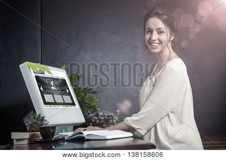 Composite image of build website interface against smiling woman using a computer smiling casual woman posing at computer desk
