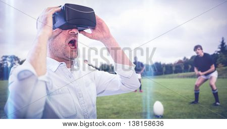 Businessman holding virtual glasses against rugby players training on pitch