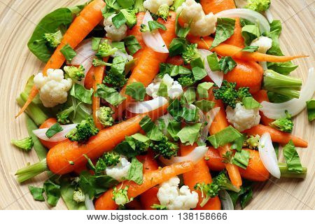 Fresh salad with baby carrots on wooden plate, top view