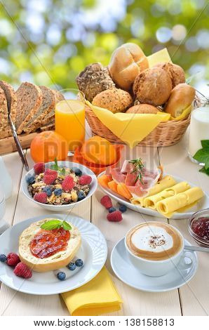 Outside served breakfast in summer with a cup of cappuccino and a large selection of food