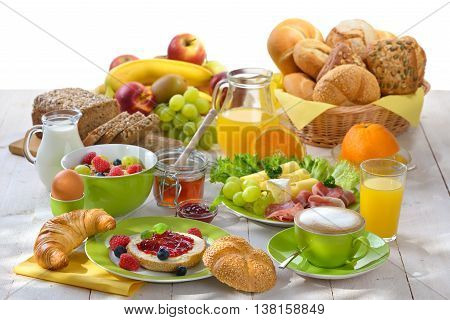 Breakfast table with a cup of cappuccino and a large selection of food against a white background