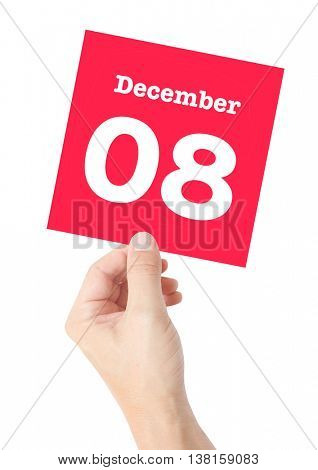 December 8 written on a card held by a hand