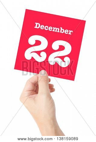 December 22 written on a card held by a hand