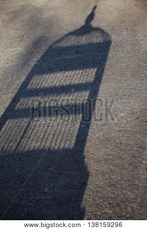 staged concept image of a birdcage shadow on concrete during sunset - representing freedom or being caged