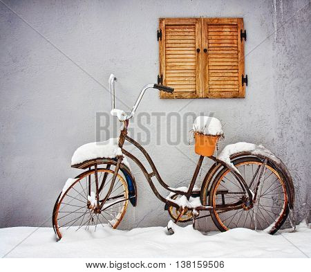 an old bicycle with a plant on it in the winter covered in snow on a deck