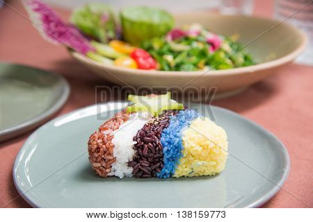 Rice turnovers (brown white purple blue yellow) on table with food blurred background.