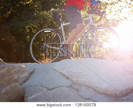 a person on a mountain bike with on top of a rock ledge toned with a retro vintage instagram filter app or action effect