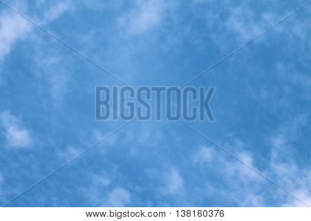 a clean background of blue sky with soft wispy white clouds