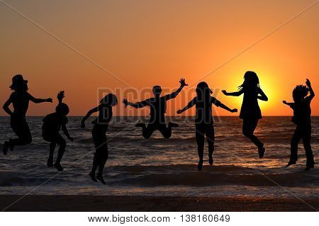 Black children silhouettes jumping at sunrise on the beach