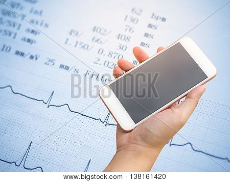 Smartphone on hand with electrocardiogram background .