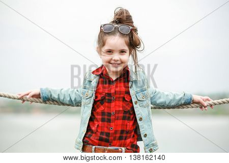 Little girl wearing stylish clothes outdoors. Fashion kid concept