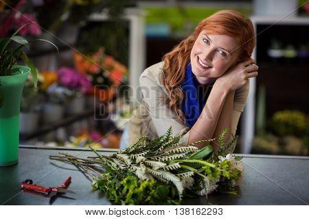 Portrait of happy female florist leaning in flower shop