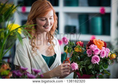 Smiling female florist preparing flower bouquet in flower shop