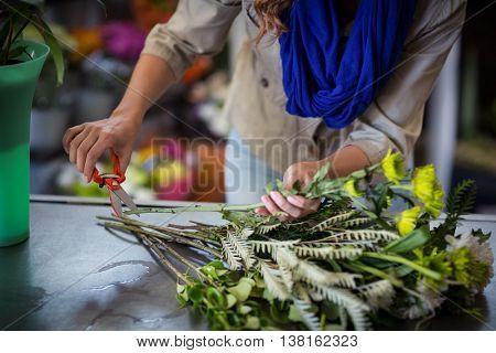 Female florist trimming flower stem at flower shop