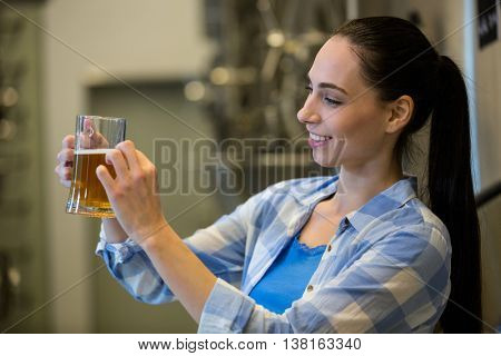 Close-up of female brewer testing beer at brewery