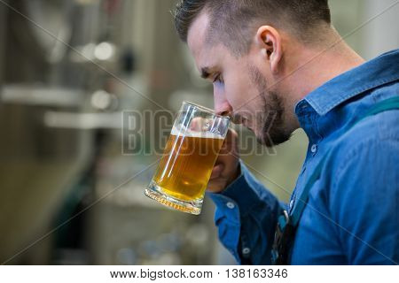 Close-up of brewer testing beer at bewery