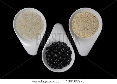 White rice, black beans and manioc flour -  ingredients of Brazilian feijoada - on white spoons over black background. Food concept and idea.