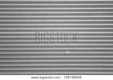 A corrugated fence of silver metal sheets with screw. Texture of metal fence