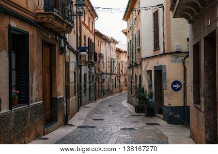Narrow winding streets in historical town part of Pollensa with its traditional stone houses Mallorca Spain