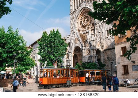 Port de Soller Mallorca Spain - May 26 2016: Old tram in Soller in front of medieval gothic cathedral with huge rose window Mallorca Spain