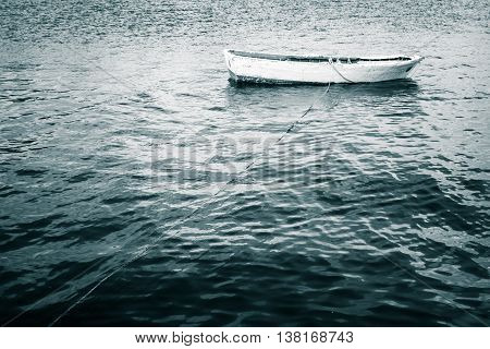 White Wooden Fishing Boat Floats On Still Sea