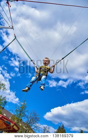 Boy flies against the sky jump on the trampoline