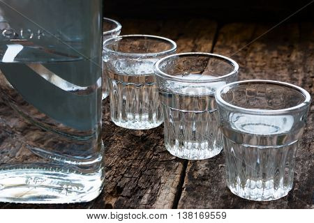 Bottle Of Vodka And Shot Glasses On A Wooden Background Close Up
