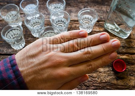 man refuses to vodka stop alcoholism on wooden background