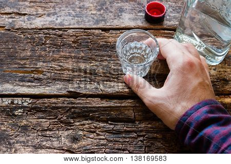 man holding a glass of vodka on wooden background