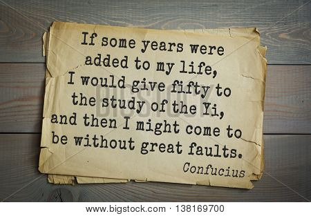 Ancient chinese philosopher Confucius quote on old paper background. If some years were added to my life, I would give fifty to the study of the Yi, and then I might come to be without great faults.