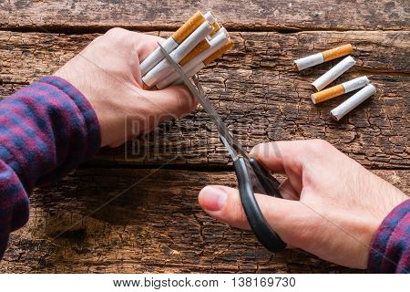 man cuts a cigarette with scissors on wooden background