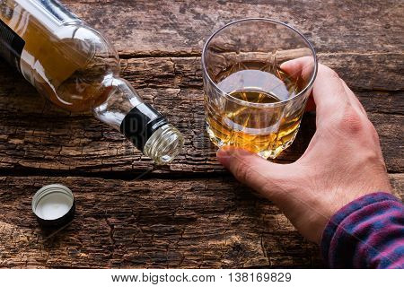 Alcoholic Holding A Glass Of Alcohol Next To An Empty Bottle