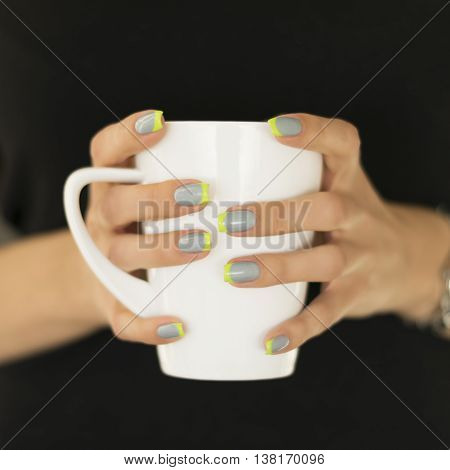 Woman in the black sweater holding in her hands with a bright nail polish white cup, closeup.