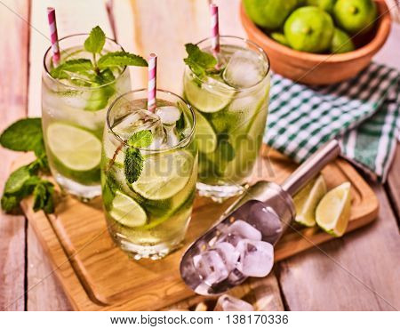 Alcohol drink. On wooden boards three glasses with straw alcohol drink and ice cubes. A drink number hundred thirteen cocktail mohito and scoop with glue bowl. Country life. Outdoor. Light background.
