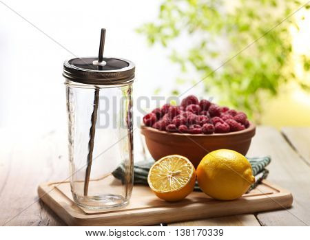 Beverage preparation. On wooden boards is clear jar glass with steel straw and lemon and raspberry bowl. Country ice cold drink beverage stewed fruit number hundred twenty five with raspberry outdoor.