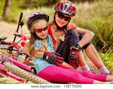 Bikes cycling family. Happy mother and daughter are sitting oncountry road near bicycles. Cycle racing concept.